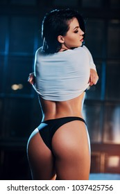 Young sexy woman standing on night window background with warm and cold lights. Focus on buttocks.