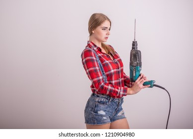 Young sexy woman stands near the white wall and holds a drill. The girl in shorts and a plaid shirt works as a puncher. A woman makes repairs with a tool.