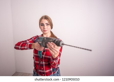 Young sexy woman stands near the white wall and holds a drill. Girl in shorts and a plaid shirt takes aim with a puncher. A woman makes repairs with a tool.