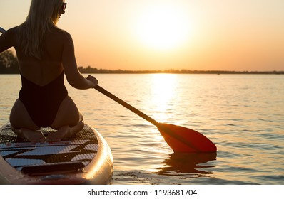 Young sexy woman swimming on stand up paddle board.Water sports , active lifestyle.