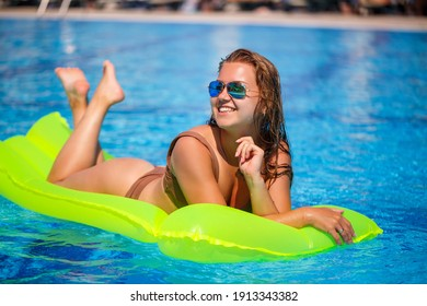 Young sexy woman in a swimsuit swims in the pool on an inflatable mattress. Girl in sunglasses with a smile on faces in a blue pool on vacation