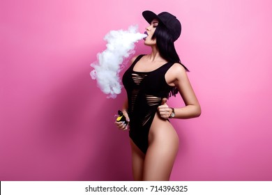 Young sexy woman is vaping. A cloud of vapor. Studio shooting.