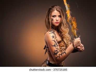 Young sexy woman warrior holding fire sword in hands with long healthy hair.