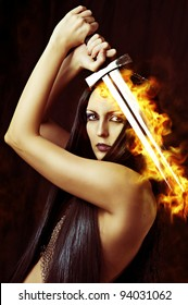 Young sexy woman warrior holding fire sword in hands with long healthy black hair.