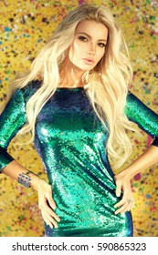 Young sexy woman wearing blue green shiny sheath dress with sequins, standing against yellow background. Party concept. Pretty slim blonde girl posing in sun light.