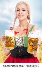 young sexy woman wearing a dirndl with two beer mugs with the blue sky and field in the background