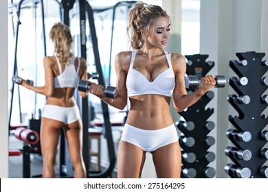 Young sexy woman in white sport wear lifting dumbbells in the gym