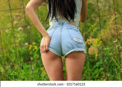 A young sexy woman's behind in tight blue hot pants shorts grabbing her bum with her own fingers