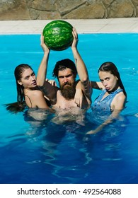 young sexy women or girls with pretty face and wet hair and bearded man swimming in pool with blue water holds green watermelon sunny summer day outdoor