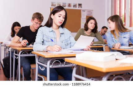 Young shcoolgirl is learning and answering the question on paper in the classroom