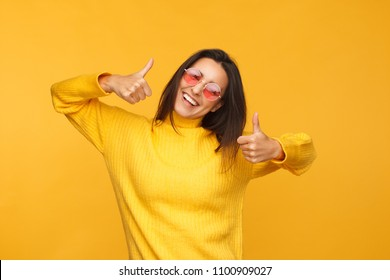 Young shining model in yellow sweater and sunglasses showing thumbs up looking at camera.