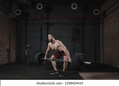 c5e59ab9c2a3 Young shirtless athlete lifting heavy barbell at crossfit gym. Handsome man  practicing powerlifting deadlift exercise