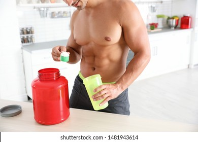 Young shirtless athletic man preparing protein shake in kitchen, closeup view