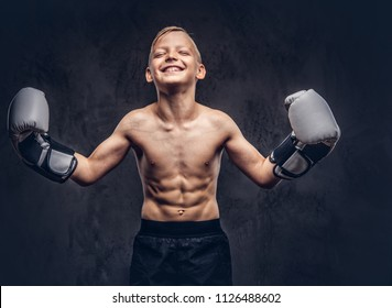 Young shirtless boy boxer with boxing gloves have fun while posing in a studio. Isolated on the dark textured background.