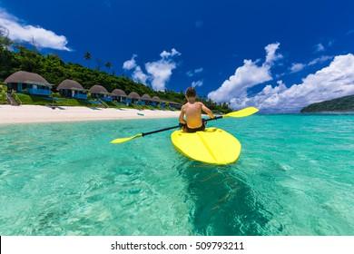 Young shirtless caucasian boy kayaking at tropical sea on yellow kayak