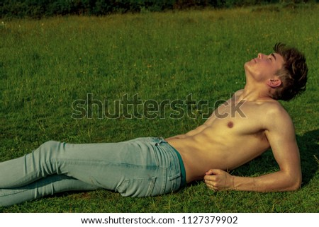 Young shirtless male adult laying in the sunshine on a warm summer's day