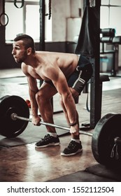 Young shirtless man doing deadlift exercise at gym. motivation.