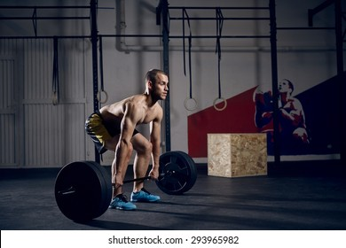 Young shirtless man doing deadlift exercise at gym