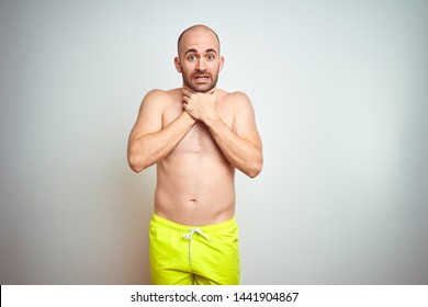 Young shirtless man on vacation wearing yellow swimwear over isolated background shouting and suffocate because painful strangle. Health problem. Asphyxiate and suicide concept.