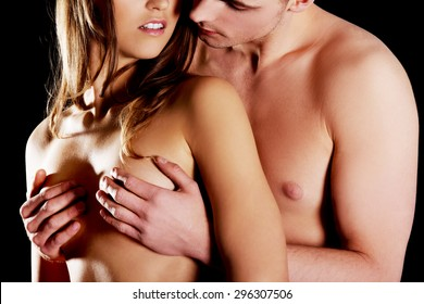 Young shirtless man touching woman's breast.