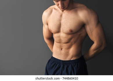 Young shirtless muscular bodybuilder posing on gray background.