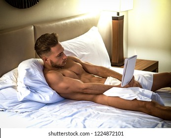 Young shirtless muscular man lying in bed and reading a book