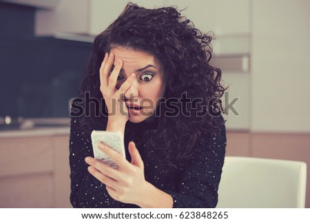 Young shocked anxious woman looking at phone seeing bad news photos text message with scared emotion on face