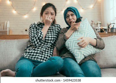 Young shocked asian women friends watching TV horror movie sitting on couch at home kitchen. islam girl with japanese roommate spending leisure time together. scared ladies by thriller film hiding.