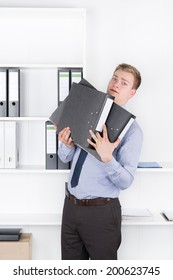 Young shocked businessman is holding several files in his arms while standing in front of a shelf in the office. The man is looking to the camera.