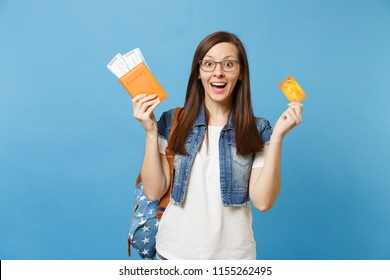 Young shocked excited woman student with backpack spread hands holding passport boarding pass ticket credit card isolated on blue background. Education in university college abroad. Air travel flight