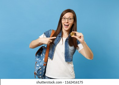 Young shocked excited woman student in glasses pointing index finger on bitcoin, metal coin of golden color isolated on blue background. Future currency. Education in high school university college