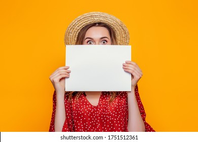 A young shocked girl in a summer red dress, a straw hat, holds an A4 empty poster and covers her face. Surprised woman shows a poster, canvas, white sheet of paper isolated over orange background
