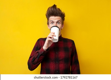 young shocked guy drinks invigorating coffee and is surprised at a yellow isolated background, a man drinks an energy drink