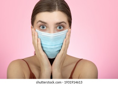 Young shocked woman in blue medical mask on pink backgraund. Beauty during quarantine and isolation