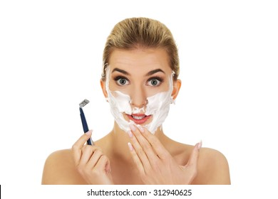 Young shocked woman shaving her face with a razor, isolated on white