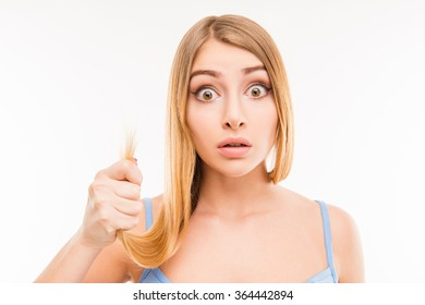 Young shocked woman showing her damaged split ends