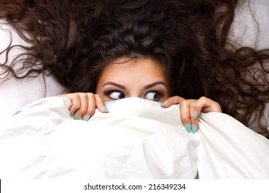young shocking  woman with beautiful brown  dishevelled curls hair in the bed