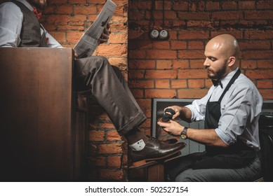young shoeshiner polishing footwear in front of the client