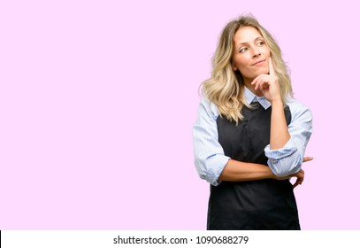 Young shop owner wearing black apron thinking and looking up expressing doubt and wonder