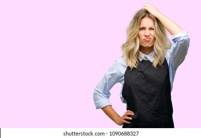 Young shop owner wearing black apron doubt expression, confuse and wonder concept, uncertain future