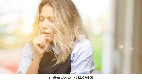 Young shop owner wearing black apron sick and coughing, suffering asthma or bronchitis, medicine concept