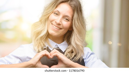 Young shop owner wearing black apron happy showing love with hands in heart shape expressing healthy and marriage symbol
