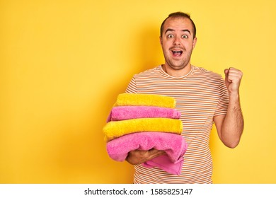 Young shopkeeper man holding folded towels standing over isolated yellow background screaming proud and celebrating victory and success very excited, cheering emotion