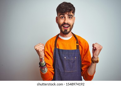 Young shopkeeper man with tattoo wearing apron standing over isolated white background celebrating surprised and amazed for success with arms raised and open eyes. Winner concept.