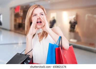 Young shopping woman with colored gift bags screaming out loud in the mall