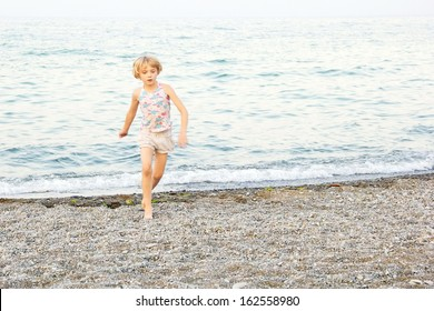 A young, short blond hair, girl, running and playing on a rocky Lake Ontario beach at dusk, at Centennial Park, Hamilton, Ontario, Canada.  Motion visible on hands and arms.