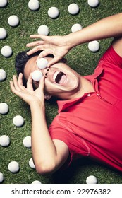 Young shouting male golf player in red shirt lying on green next to several golf balls and covering his eyes with two golf balls.
