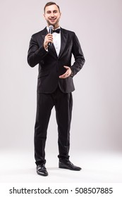 Young Showman presenter with microphone against white background.Showman concept.