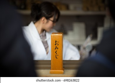 "Young shrine maiden handing Omikuji over during Japanese new year in Kamakura. The sign on the wooden box reads ""Omikuji"" = fortune-telling paper strips."