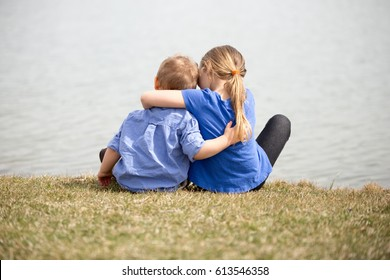 Young sibling boy and girl looking at the lake holding each other.